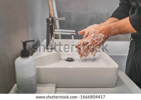 Washing hands with soap and hot water at home bathroom sink man cleansing hand hygiene for coronavirus outbreak prevention. Corona Virus pandemic protection by washing hands frequently. #1666804417