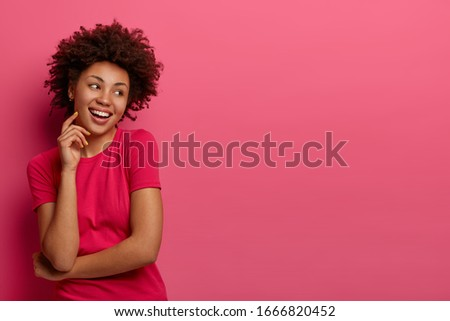 Isolated shot of pretty woman with natural curly hair, looks aside and has dark skin, touches face, smiles toothily, wears casual t shirt, poses against pink background, blank space for your advert #1666820452