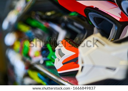 Motorcycles and accessories in modern motorcycle shop. Biker stuff. Helmets on wooden background. Selective focus.