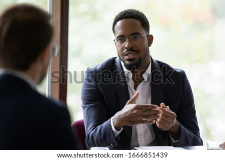 Confident concentrated African American male employee talk with colleague explain thought or idea, focused biracial businessman speak with coworker or partner, brainstorm at office boardroom meeting Royalty-Free Stock Photo #1666851439