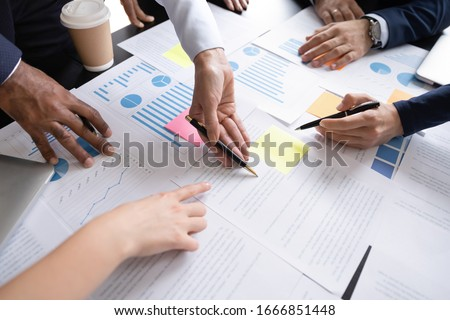 Close up top view of diverse businesspeople cooperate work together discussing company financial statistics, multiracial colleagues employees collaborate brainstorm with finance document at meeting #1666851448