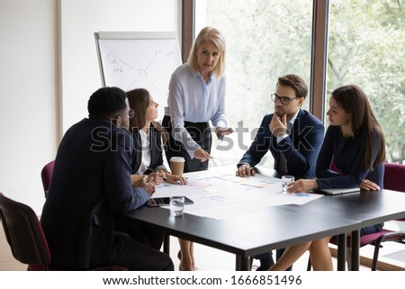 Concentrated middle-aged female leader head team meeting with multiracial colleagues in office, diverse businesspeople brainstorm discuss business project at briefing together, cooperation concept #1666851496