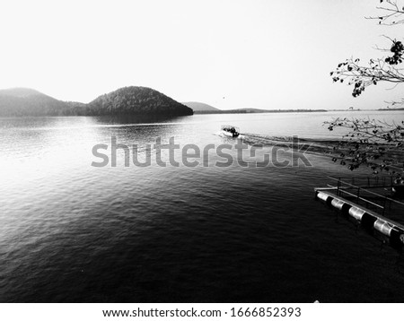 chandil dam jharkhand, pic with vista effect which includes river, mountain, boat, tree and sky..timing is amazing as the boat is in the middle and the water around it is still except behind the boat.