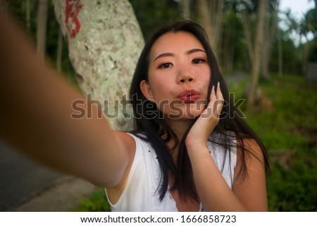 young beautiful and happy Asian Korean woman taking selfie portrait picture with mobile phone smiling cheerful and relaxed outdoors at tropical jungle  exploring place in holidays travel