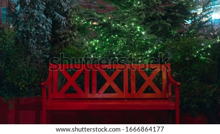 The red bench.A large, bright, red bench against a background of green trees and Christmas trees covered with snow and decorated with luminous garlands. Symmetrical photo.The concept of rest.
