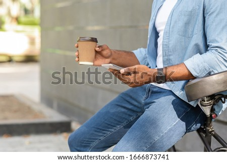 Unrecognizable black guy leaning on bicycle, browsing smartphone and drinking takeaway coffee outdoors #1666873741