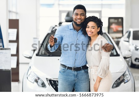 Joyful Black Couple Holding New Car Key Smiling At Camera Posing Standing Near Luxury Auto In Dealership Store Royalty-Free Stock Photo #1666873975