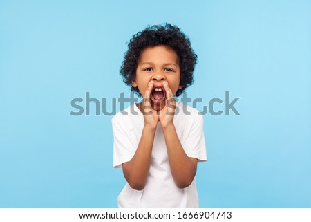 Attention! Portrait of little boy with curly hair in white T-shirt holding hands near wide open mouth and shouting loudly, screaming announcement. indoor studio shot isolated on blue background #1666904743