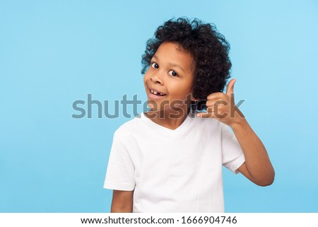 Call me! Portrait of funny little boy holding fingers shaped like telephone near head, communicating by phone, looking at camera with playful smile. indoor studio shot isolated on blue background #1666904746
