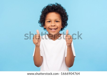 Like! Portrait of happy little boy with curly hair in white T-shirt smiling at camera and doing thumbs up gesture, showing agree cool approval sign. indoor studio shot isolated on blue background #1666904764