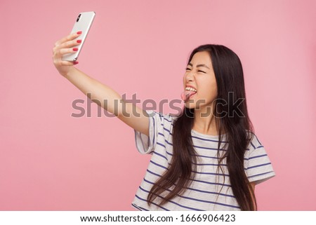 Portrait of childish naughty asian girl with brunette hair taking selfie and demonstrating tongue, making face having fun while doing photo for blog. indoor studio shot isolated on pink background