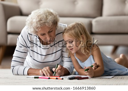 Caring senior grandmother lying on floor with cute little preschooler granddaughter drawing together, loving mature grandparent play have fun with small grandchild painting at home, education concept