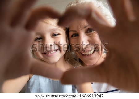 Self-portrait picture of smiling mature grandmother and cute little preschooler granddaughter make heart with hands pose look at camera together, happy senior granny and small grandchild take selfie