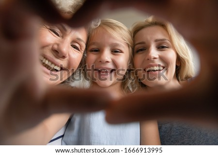 Portrait of smiling three generations of women have fun posing for self-portrait picture make heart gesture, happy overjoyed little girl make selfie with young mom and senior grandmother