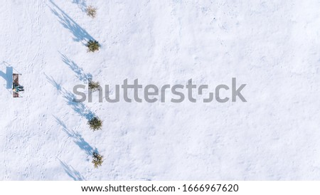 Beautiful landscape with trees, benches, hard shadow and snow. Snowy forest. Outside travel background. Cold weather. Aerial view of winter park. Drone view. Stock photo.