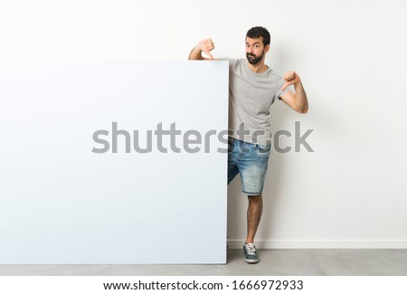 Young handsome man with beard holding a big blue empty placard showing thumb down #1666972933