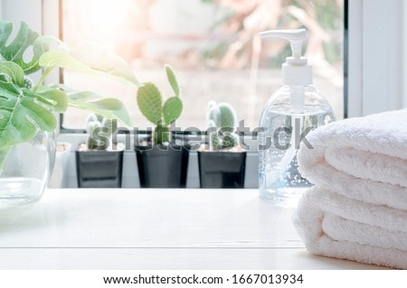 Stack of Clean towels with bottle of alcohol rub gel and houseplant on white wooden table in kitchenroom. Copy space. #1667013934