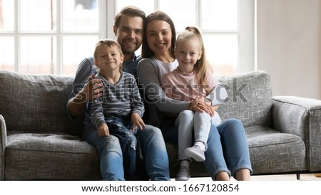 Portrait of young married couple resting on sofa, holding on lap adorable kids siblings. Happy loving bonding family of four relaxing on couch, posing for photo together in modern living room. #1667120854