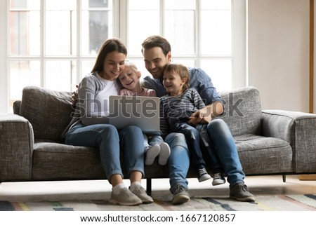 Happy young couple resting with children siblings on sofa, watching cartoons comedian movie on laptop. Overjoyed spouses having fun with joyful cute kids son daughter, using computer at home.