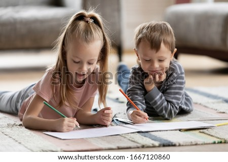 Playful adorable blonde girl lying on carpet floor with younger brother, drawing pictures together in paper album. Interested two little children siblings involved in creative activity hobby at home.