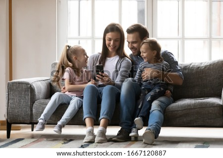 Full length joyful family of four sitting on couch, watching funny video together at home. Smiling young woman taking selfie photo with affectionate husband and cute kids son daughter on smartphone. #1667120887