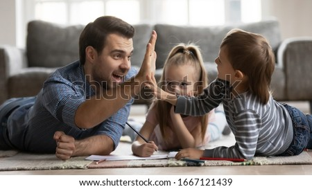 Close up father giving high five to excited little kid son after finishing drawing picture. Smiling dad lying on floor carpet with cute children siblings, enjoying creative activity at weekend time.