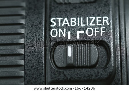 """This photo shows a closeup to a lens stabilizer button on the """"On"""" position .  #166714286"""