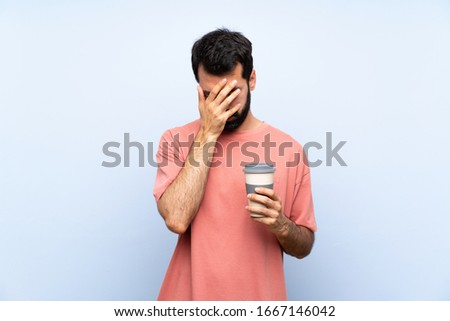 Young man with beard holding a take away coffee over isolated blue background with tired and sick expression #1667146042