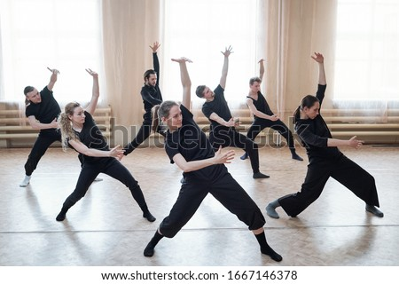 Three fit girls and four guys in black activewear standing on the floor with outstretched legs and bent knees while exercising in dance studio Royalty-Free Stock Photo #1667146378