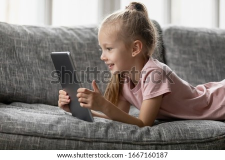 Smiling little girl lying on comfortable couch, enjoying playing online game on digital tablet computer. Addicted to technology, happy small kid using funny applications, web surfing information.