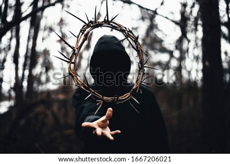 Moody Conceptual Photo of Person Throwing Crown of Thorns Wearing Jacket with Hood in Dark Moody Forest, Christian Faith