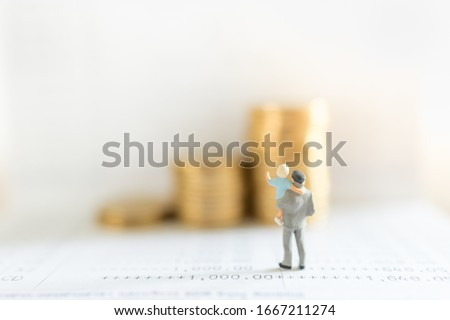 Business, Money, Saving, Security and Family Concept. Close up of father and child standing on bank passbook and looking to stack of gold coins with copy space. #1667211274