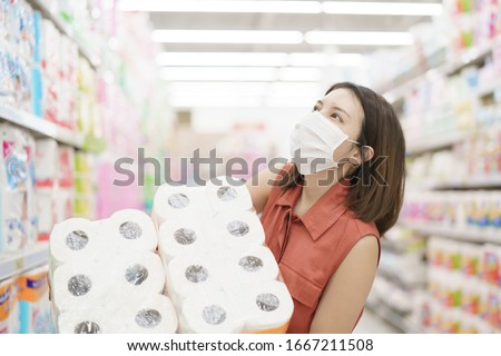 covid-19 spreading outbreak. Woman in medical protective mask panic buying tissue paper. Fear of coronavirus. #1667211508