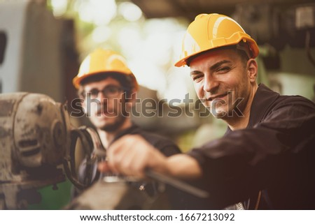 Scene of industrial workers wearing jumpsuit and yellow safety hat turn his face to camera and smile feeling like happy in the factory atmosphere, Concept life with insurance is sustainable working. #1667213092