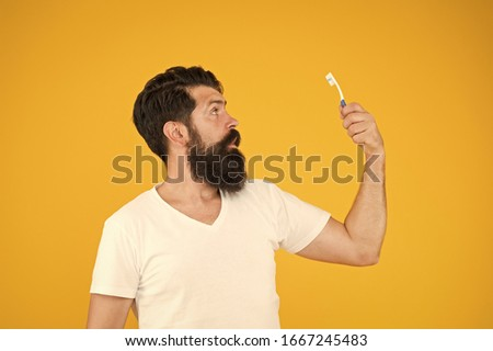 Brush your teeth. Bearded man look at tooth brush. Daily oral hygiene. Dental health habits. Brush properly and regularly. Tooth brushing and cleaning. Clean teeth. Dont rush when you brush. #1667245483