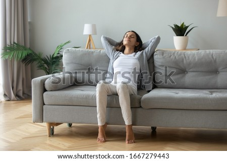 Happy millennial girl sit relax on comfortable couch in living room hands over head, peaceful young woman rest on cozy sofa at home take nap dream with closed breathe fresh air, stress free concept #1667279443
