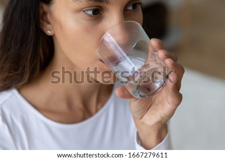 Close up of young Caucasian woman hold glass drinking pure mineral water maintain body balance, millennial girl enjoy clear still aqua fell thirsty at home, healthy lifestyle, good habit concept #1667279611