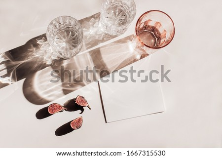 Summer stationery still life scene. Glasses of water, cut figs fruit. Pink table background in sunlight. Blank business, greeting card, invitation mockup scene. Long harsh shadows. Flat lay, top view #1667315530