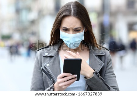 Front view portrait of a scared girl wearing protective mask avoiding contagion reading news on her smart phone on a city street Royalty-Free Stock Photo #1667327839