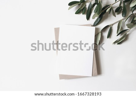 Summer wedding stationery mock-up scene. Blank vertical greeting card, craft paper envelope and olive branches isolated on white table background. Feminine Mediterranean flat lay, top view. #1667328193
