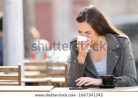 Sick woman blowing her nose with tissue sitting on a coffee shop terrace #1667341345