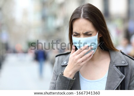 Portrait of a sick woman with protective medical mask coughing on city street #1667341360
