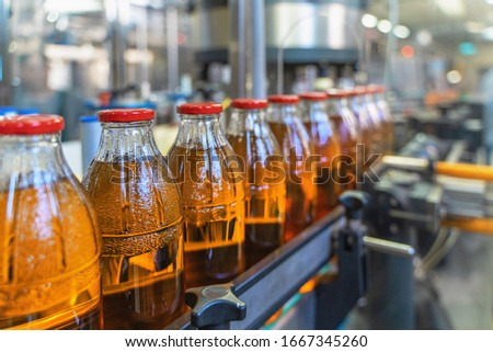 Conveyor belt, juice in bottles on beverage plant or factory interior, industrial production line, selective focus. Royalty-Free Stock Photo #1667345260