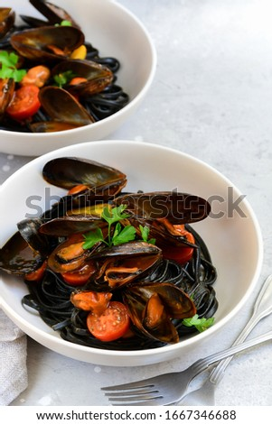 Black spaghetti. Black seafood pasta with mussels. Mediterranean delicacy food. black pasta with cuttlefish ink, recipe Italian food, spanish food. selective focus and copy space #1667346688