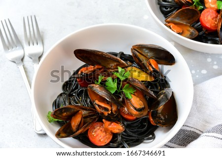 Black spaghetti. Black seafood pasta with mussels. Mediterranean delicacy food. black pasta with cuttlefish ink, recipe Italian food, spanish food. selective focus and copy space #1667346691