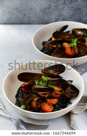 Black spaghetti. Black seafood pasta with mussels. Mediterranean delicacy food. black pasta with cuttlefish ink, recipe Italian food, spanish food. selective focus and copy space #1667346694