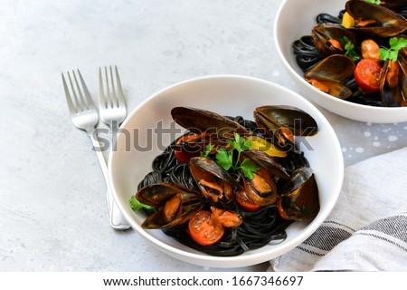 Black spaghetti. Black seafood pasta with mussels. Mediterranean delicacy food. black pasta with cuttlefish ink, recipe Italian food, spanish food. selective focus and copy space #1667346697