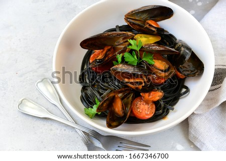 Black spaghetti. Black seafood pasta with mussels. Mediterranean delicacy food. black pasta with cuttlefish ink, recipe Italian food, spanish food. selective focus and copy space #1667346700