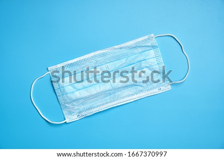 Protective methecin mask on the face on a blue background. Top view. #1667370997