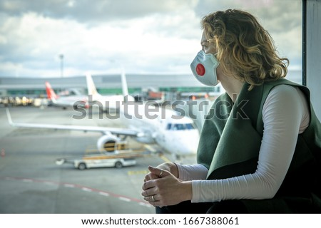 Woman with a mask on her mouth protects against the virus. She looks sad through the window at the airport on planes. Aerial connections canceled due to a coronavirus #1667388061